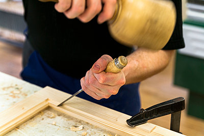 Frame-maker working on a wooden frame with mallet and chisel - p300m1023085f by Tom Chance