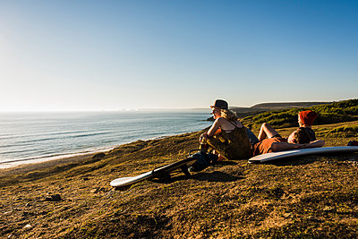 Three friends with surfboards relaxing at seaside - p300m1188913 by Uwe Umstätter