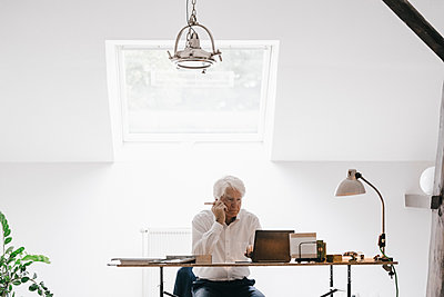 Senior businessman working with laptop in his office - p300m1228260 by Kniel Synnatzschke