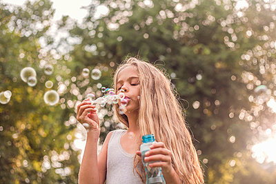 Cute girl blowing bubbles in park - p300m2239986 by LOUIS CHRISTIAN