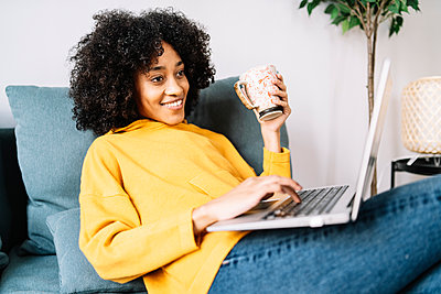 Young woman using laptop while holding mug at home - p300m2277200 by COROIMAGE