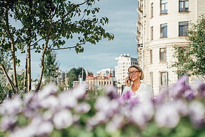 Smiling female professional looking away while talking on smart phone at office park - p300m2294228 by Vasily Pindyurin