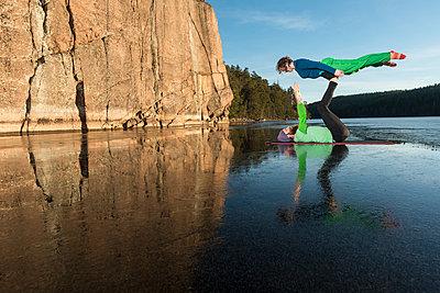 Couple doing yoga on frozen lake - p312m1472251 by Fredrik Schlyter