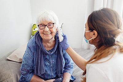 Nurse checking woman's temperature at home - p312m2299631 by Plattform