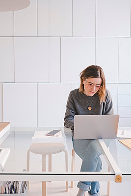 Young female entrepreneur using laptop at desk in design studio - p426m1580175 by Maskot