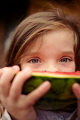 Girl eating watermelon outdoors - p429m1450366 by Emma Kim