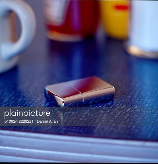 Feuerzeug auf einer Tischplatte - p1082m2228221 von Daniel Allan