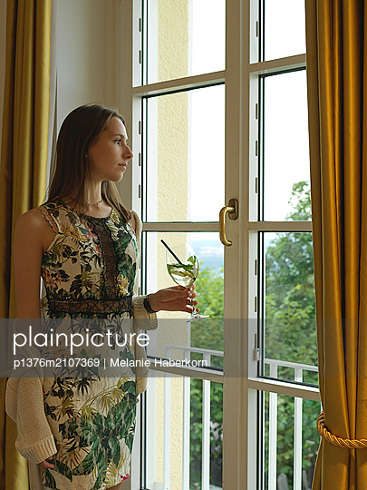 Young woman looking out of window - p1376m2107369 by Melanie Haberkorn