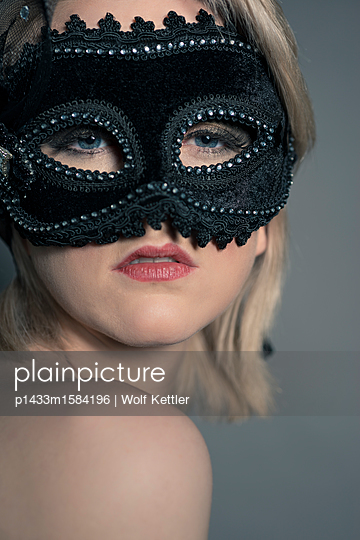 Glamorous blonde Woman wearing a black velvet and lace face mask, looking at camera. - p1433m1584196 by Wolf Kettler