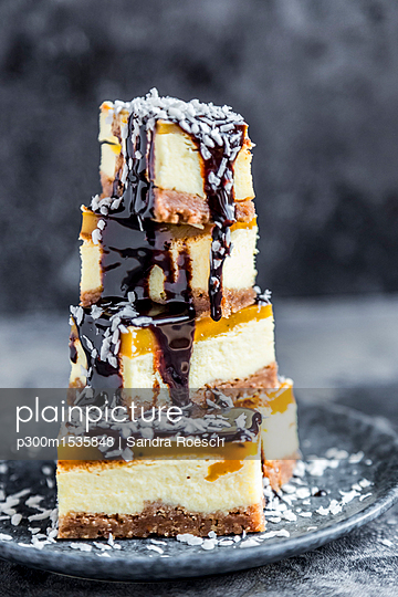 Cheesecake with mango orange cream, chocolate sauce and coconut flakes - p300m1535848 by Sandra Roesch