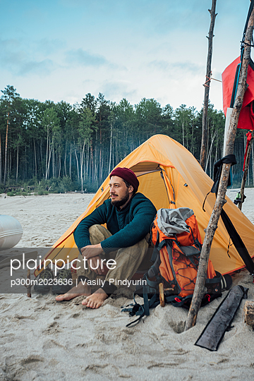 Backpacker sitting in front of his tent on the beach - p300m2023636 von Vasily Pindyurin