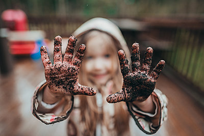 Portrait of girl showing dirty hands - p1166m1474555 by Cavan Images