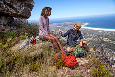 Young hiking couple takes a break in the mountains - p1355m1574191 by Tomasrodriguez