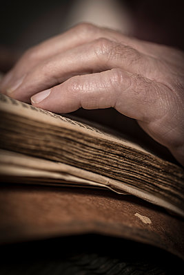 Old male hand on an open antique book or prayer book. - p1433m1586213 by Wolf Kettler