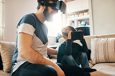Father and little son sitting on the couch at home wearing virtual reality glasses - p300m1581519 by Zeljko Dangubic