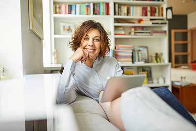 Portrait of smiling mature woman with tablet sitting on couch at home - p300m1587876 by Philipp Nemenz