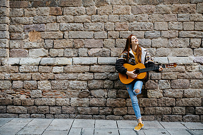 Red-haired woman playing the guitar in the city - p300m2058976 by Josep Rovirosa