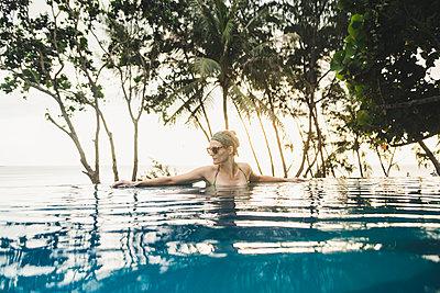 Woman in infinity pool at sunset, Nai Thon Beach, Phuket, Thailand - p300m2166354 by Christophe Papke