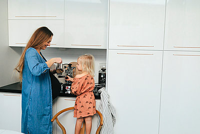 Mother with daughter making coffee - p312m2050285 by Anna Rostrom