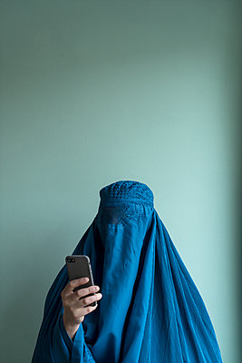 Young woman wearing burka using smartphone - p427m2092565 by Ralf Mohr