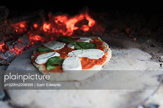 Homemade margherita pizza on stone in hot pizza oven - p1023m2208355 by Sam Edwards