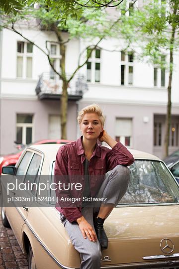 Junge Frau lehnt sich an ein Auto - p1303m1152404 von Ansgar Schwarz