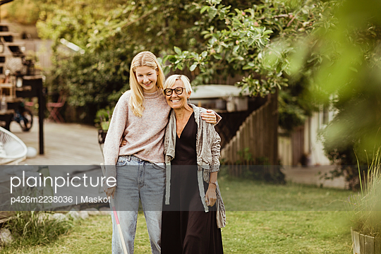 Smiling granddaughter with arm around grandmother standing in back yard - p426m2238036 by Maskot