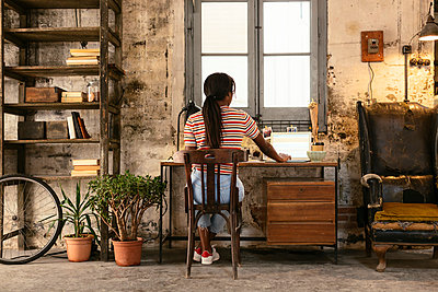 Back view of young woman sitting at desk in a loft working on laptop - p300m1580847 von Bonninstudio