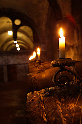 Barrels of wine in cellar lit by candlelight - p30119854f by Marc Volk