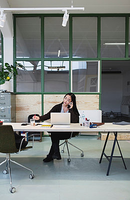Woman using smart phone at desk in creative office - p426m1407202 by Maskot