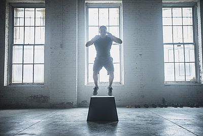 Athlete jumping on platform - p555m1411989 by John Fedele