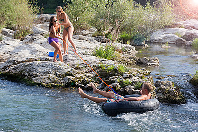 Yougn people on the riverbank have fun with swimming ring - p825m1442113 by Andreas Baum