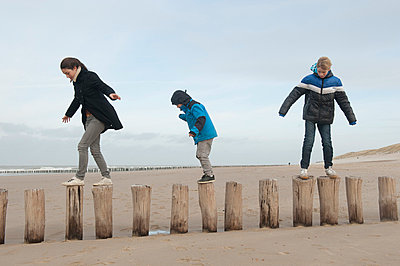 Children walking on wavebreakers - p896m835041 by Sabine Joosten