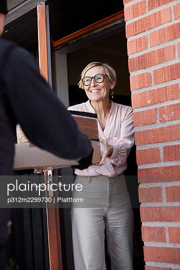 Woman having parcels delivered - p312m2299730 by Plattform