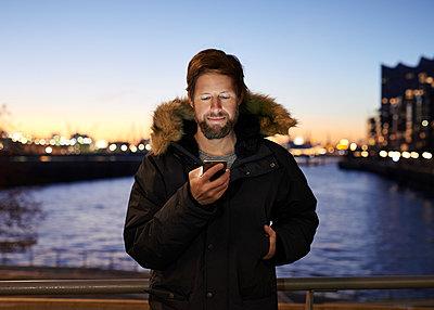 Mann mit Smartphone am Wasser - p1124m1195813 von Willing-Holtz