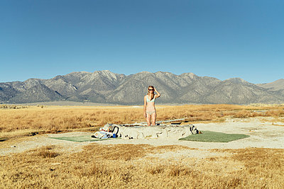 Woman in swimming pool on field by mountains against clear sky - p1166m1210066 by Cavan Images