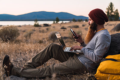 USA, North California, bearded young man using cell phone and laptop near Lassen Volcanic National Park - p300m2059143 by Kike Arnaiz