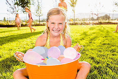 Caucasian girl playing with water balloons in backyard - p555m1415628 by Mike Kemp