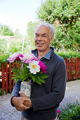 Man holding bouqet flowers - p956m1044913 by Anna Quinn