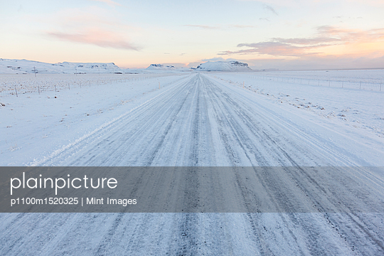 Winter landscape with snow covered rural road at twilight. - p1100m1520325 by Mint Images