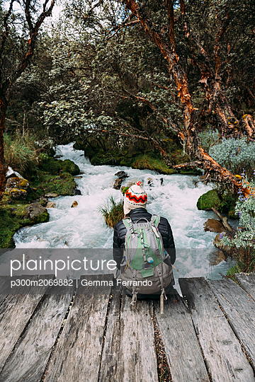 Peru, Huaraz, Man with woolly hat and backpack sitting on wooden bridge at a river - p300m2069882 by Gemma Ferrando