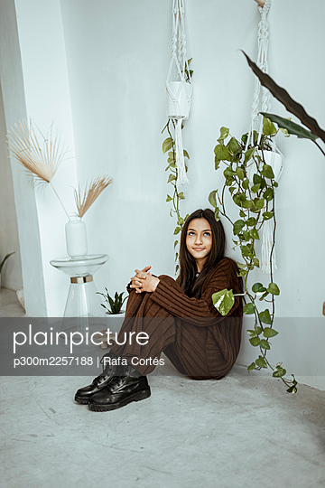 Smiling girl looking up while sitting by creeper plant against white wall at home - p300m2257188 by Rafa Cortés