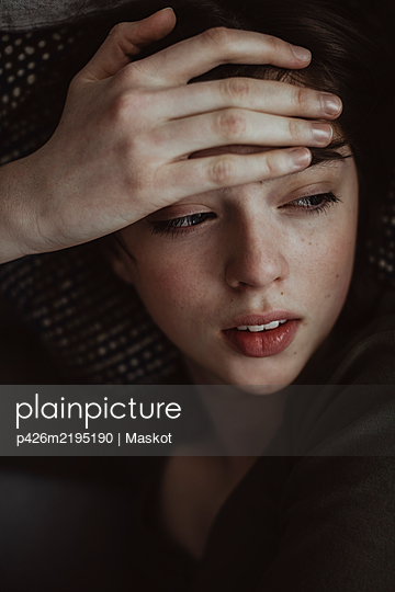 Close-up of woman with headache looking away while lying on sofa - p426m2195190 by Maskot