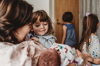 Side view of mother holding newborn son meeting siblings - p1166m2162531 by Cavan Images