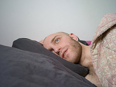 Man with bald head in bed  - p1267m2043236 by Jörg Meier