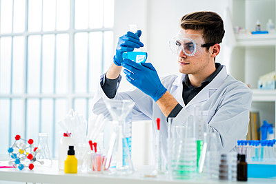 Young scientist measuring chemical in flask at laboratory - p300m2265426 by Giorgio Fochesato