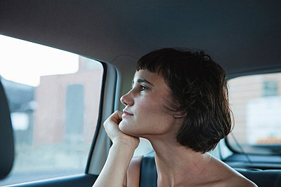 Young woman looking out of car window - p429m803074f by DUEL photography