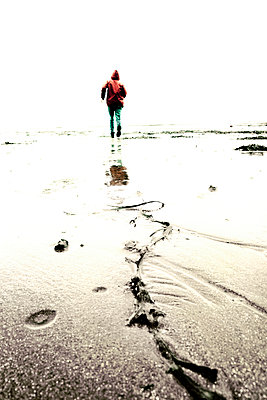 Rearview figure in red anorak running away over low tide - p597m932716 by Tim Robinson