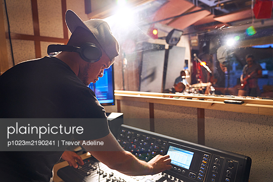 Man working at sound board in music recording studio - p1023m2190241 by Trevor Adeline