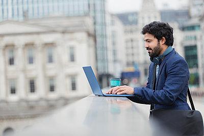 Businessman using laptop on city bridge - p1023m2208429 by Paul Bradbury